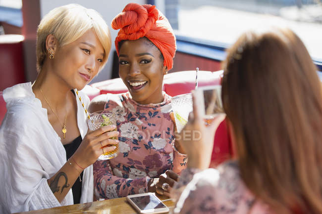 Young women friends drinking cocktails, posing for photograph in restaurant — Stock Photo