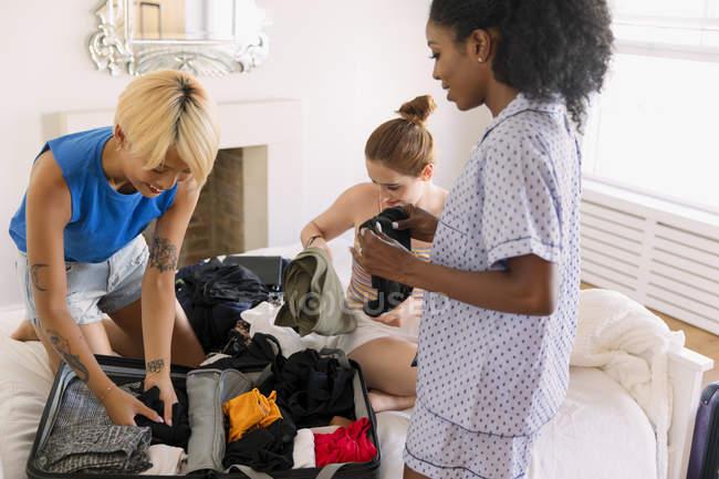 Giovani donne amici imballaggio per Spring Break in camera da letto — Foto stock