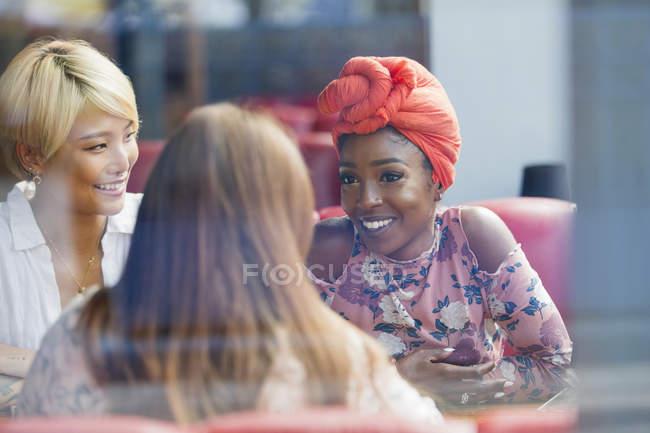 Молодые женщины друзья говорят в кафе — стоковое фото