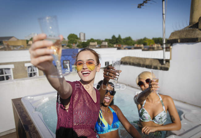 Portrait confident, carefree young women friends drinking champagne in sunny rooftop hot tub — Stock Photo