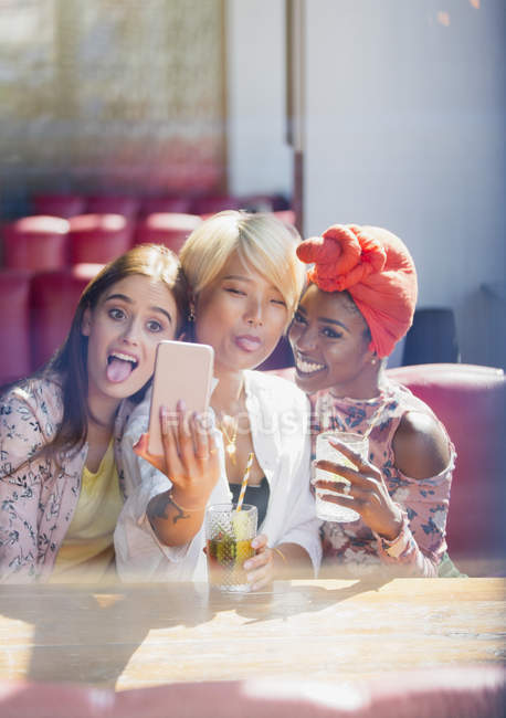 Silly, playful young women friends taking selfie with camera phone in cafe — Stock Photo