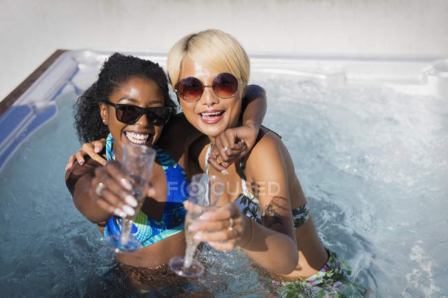 Portrait exuberant young women friends drinking champagne in sunny hot tub — Stock Photo