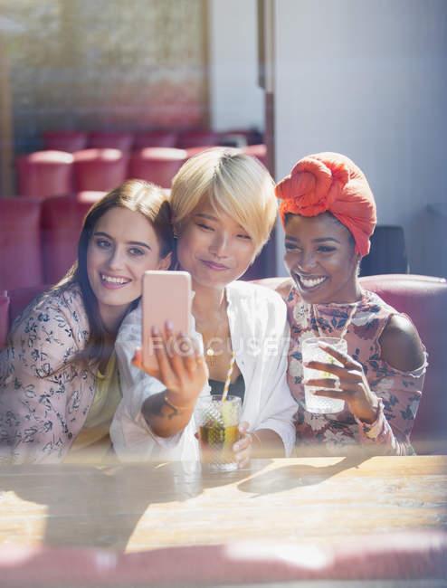 Друзья молодых женщин пьют коктейли и позируют для селфи в солнечном ресторане — стоковое фото