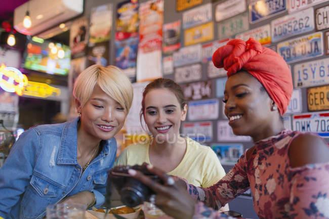 Jeunes amies utilisant un appareil photo numérique dans le bar — Photo de stock