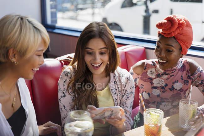 Друзья молодых женщин с помощью смарт-телефона и пить коктейли в ресторане — стоковое фото