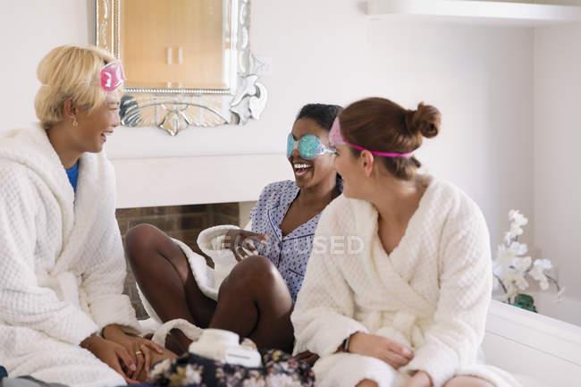 Amigos das mulheres novas que desgastam máscaras de olho no quarto — Fotografia de Stock