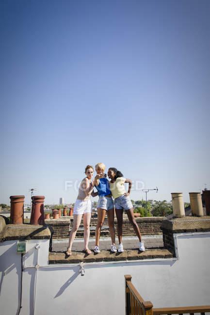 Amigos das mulheres novas que tomam o selfie com telefone da câmera no telhado ensolarado — Fotografia de Stock