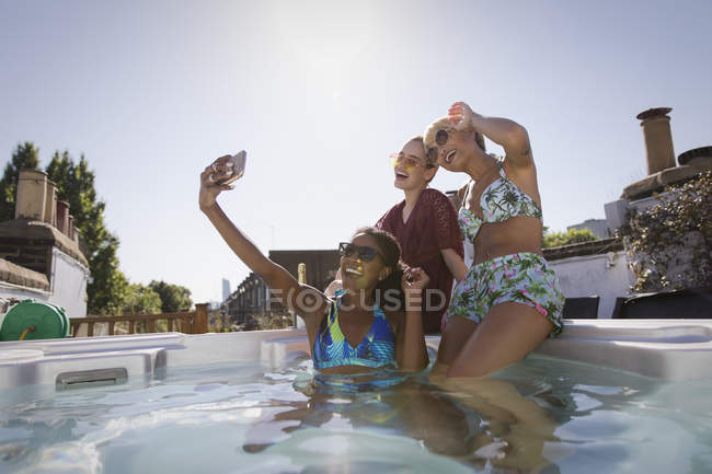 Happy, carefree young women friends in bikinis taking selfie with camera phone in sunny, rooftop hot tub — Stock Photo