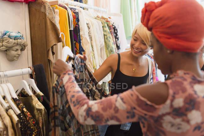 Giovani donne amiche shopping nel negozio di abbigliamento — Foto stock