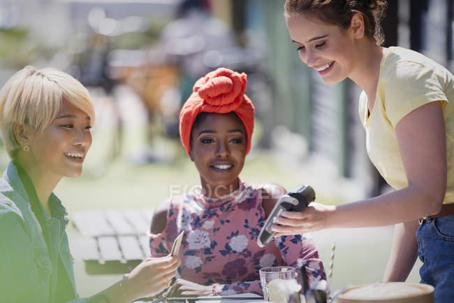 Jeune femme payant serveuse avec carte de crédit au café Sunny sidewalk — Photo de stock