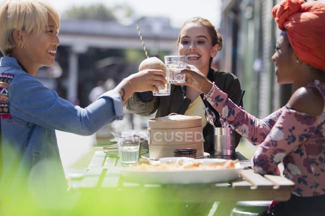 Молодые женщины пьют бокалы с водой за обедом в кафе на солнечном тротуаре — стоковое фото