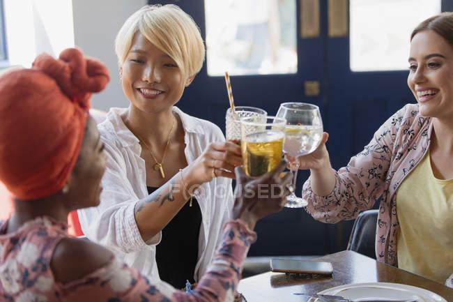 Amigos das mulheres novas que brindam vidros de cocktail na barra — Fotografia de Stock