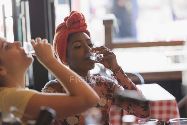 Young women friends taking alcohol shots in bar — Stock Photo