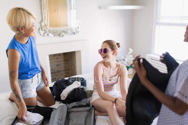 Spensierato giovani donne amici imballaggio per Spring Break in camera da letto — Foto stock