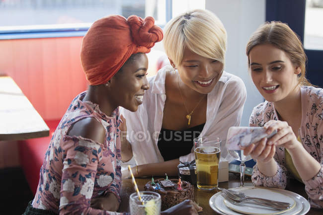 Young women friends using smart phone at restaurant table — Stock Photo