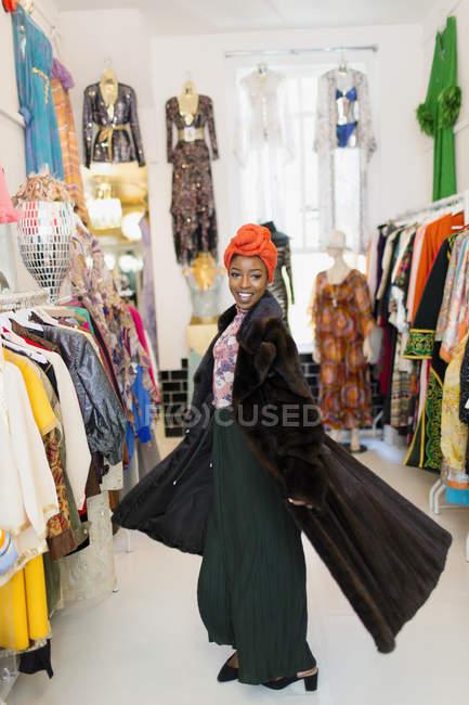 Портрет упевнений, стильна молода жінка намагається на Шуби в магазині одягу — стокове фото