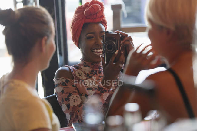 Young woman photographing friend with digital camera in cafe — Stock Photo