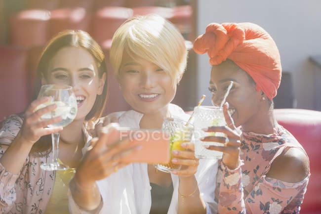Молодые женщины друзей пить коктейли и принимая selfie с смарт-телефон в Солнечный бар — стоковое фото