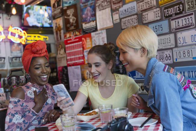 Молодые женщины друзей с помощью смарт-телефон в баре — стоковое фото