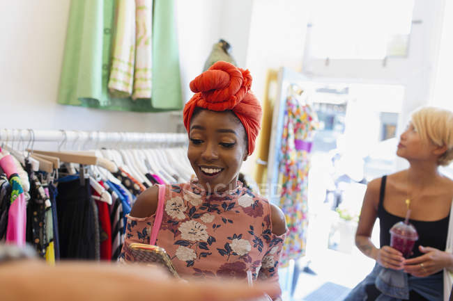 Молода жінка, використовуючи смарт-телефону в магазин одягу — стокове фото