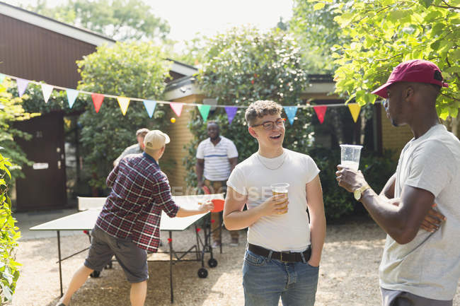 Friends drinking beer and playing ping pong in summer backyard — Stock Photo