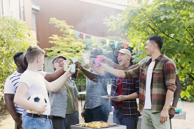 Heureux amis masculins toasting boissons sur barbecue grill dans la cour arrière — Photo de stock