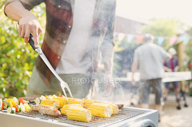 Man barbecuing corn, sausage and vegetable kebabs — Stock Photo