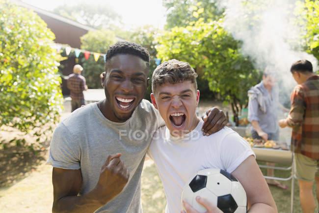 Ritratto entusiasta giovani uomini con calcio palla tifo, godendo back yard barbecue — Foto stock