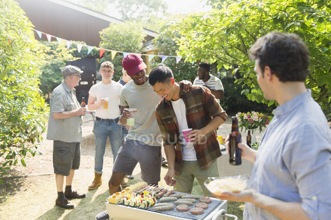 Male friends drinking beer and barbecuing in sunny summer backyard — Stock Photo