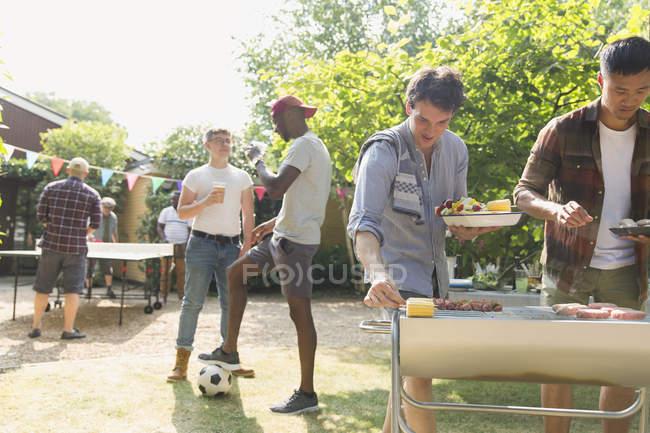 Male friends enjoying barbecue in sunny summer backyard — Stock Photo