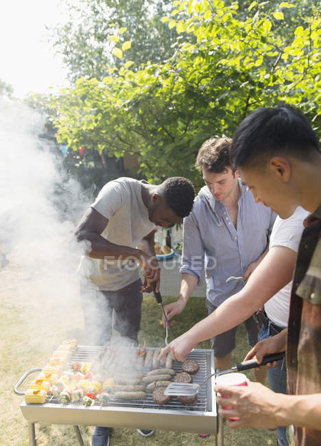Male friends at barbecue grill in sunny backyard — Stock Photo