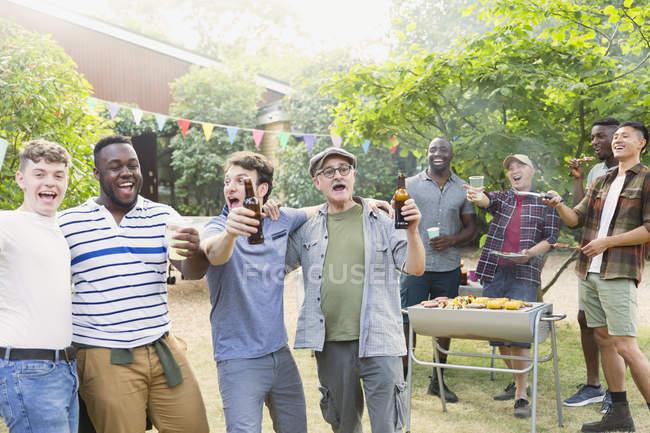 Felice, esuberante amici maschi bere birra e cantare durante il barbecue in cortile — Foto stock