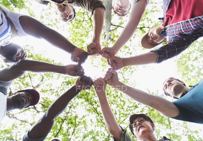 Vista abaixo dos punhos de junção do grupo do Mens no círculo, caminhando árvores — Fotografia de Stock