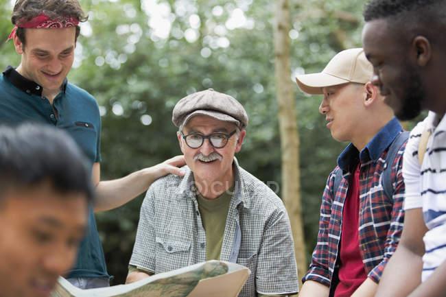 Retrato sonriente hombre con mapa en la caminata con amigos - foto de stock