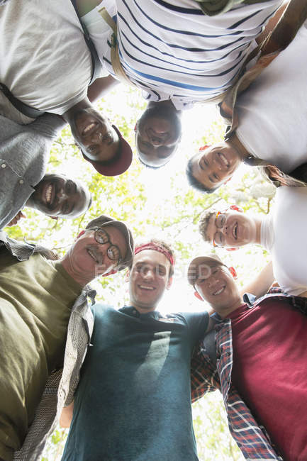 View from below mens group standing in huddle — Stock Photo