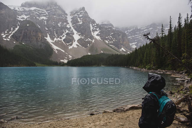 Serene hiker in rain jacket enjoying tranquil mountain and lake view, Banff, Alberta, Canada — Stock Photo