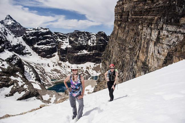 Excursionistas hembra senderismo ladera nevada de montaña, Yoho Park, Columbia Británica, Canadá - foto de stock