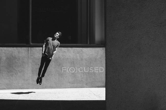 Young man jumping on urban sidewalk — Foto stock