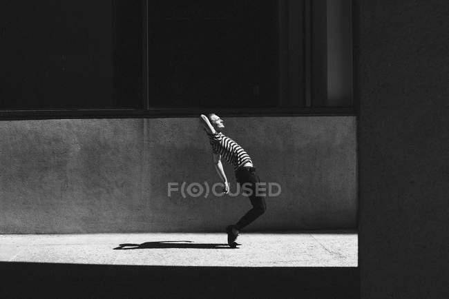 Young man dancing on urban sidewalk — Stock Photo
