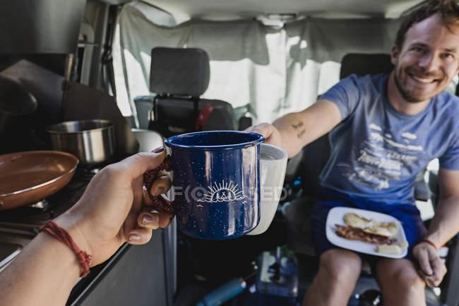 Persönliche Perspektive des Paares Toasten Kaffeetassen in Wohnmobil — Stockfoto