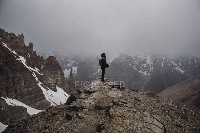 Female hiker on top of craggy, foggy mountain Banff, Alberta, Canada — Stock Photo
