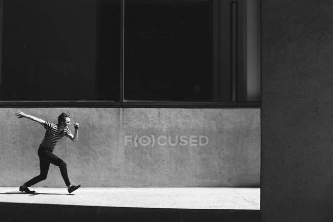 Young man walking on sunny urban sidewalk — Stock Photo