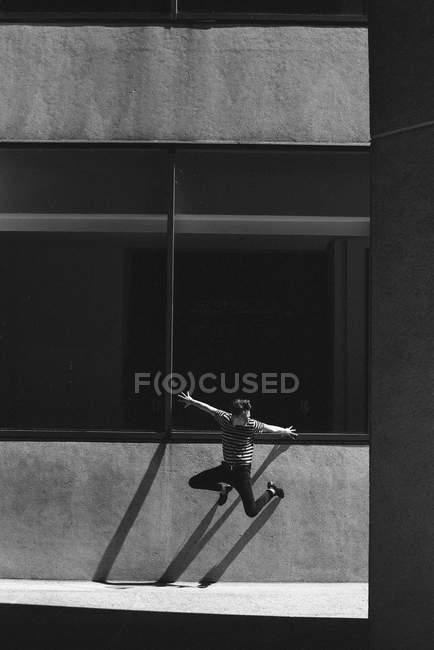 Giovane esuberante che salta contro le mura urbane — Foto stock
