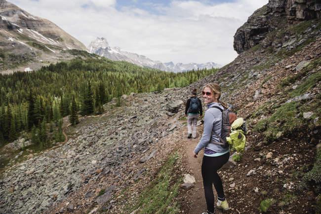 Portrait smiling woman hiking on craggy mountain trail, Yoho Park, British Columbia, Canada — Stock Photo