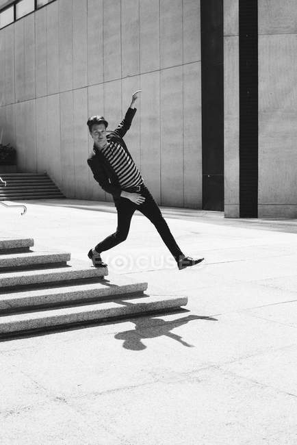 Портрет прохладный молодой человек, шагающий с городской ступеньки — стоковое фото