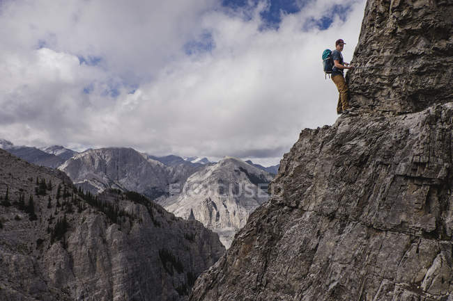 Man mountain climbing steep, craggy mountain face — Stock Photo