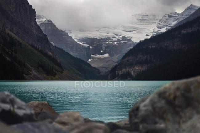 Vue panoramique montagnes majestueuses au-delà du lac bleu tranquille, Lake Louise, Alberta, Canada — Photo de stock