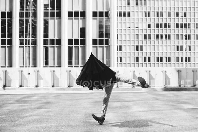 Мужчина танцует с зонтиком на голове за пределами городских зданий — стоковое фото