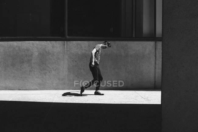 Ombre suivant l'homme marchant sur le trottoir ensoleillé — Photo de stock