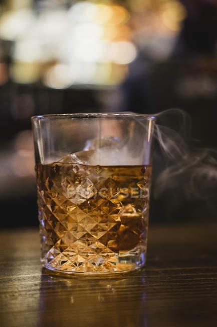 Копченый коктейль виски в бокале — стоковое фото